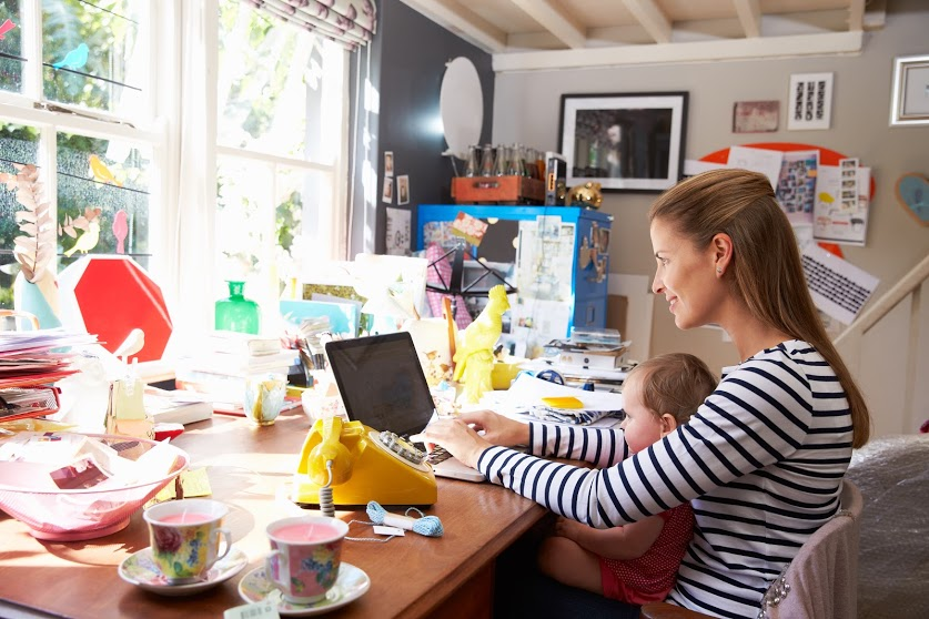 A woman working on a laptop with a baby in her lap