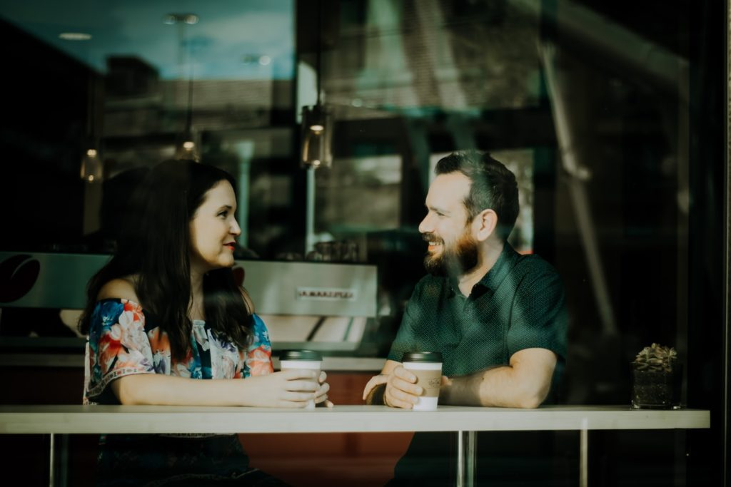 A couple sitting in a coffee shop setting talking