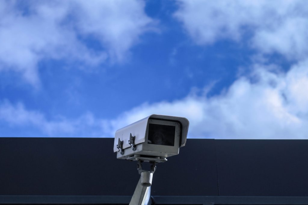A security camera posted on the top of a building